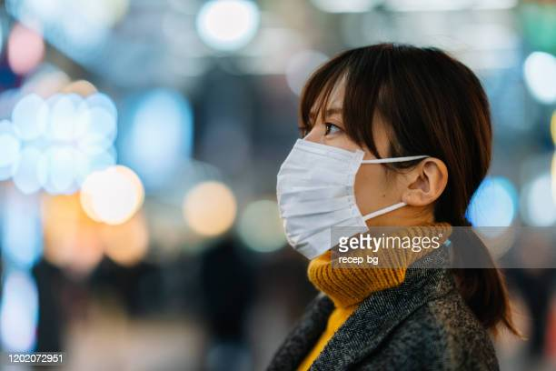portrait of young woman wearing face mask - sudden acute respiratory syndrome stock pictures, royalty-free photos & images