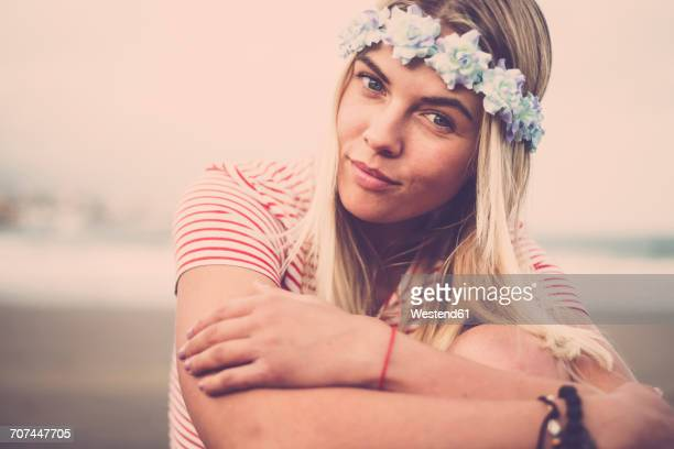 portrait of young woman wearing flowers sitting on the beach - desaturated stock pictures, royalty-free photos & images