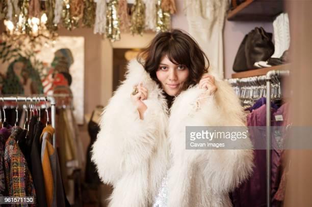 portrait of young woman wearing fur coat at boutique - pele de animal material têxtil - fotografias e filmes do acervo