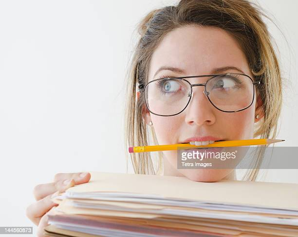 Portrait of young woman wearing glasses and holding pencil in mouth,  studio shot