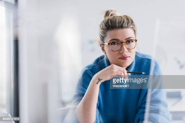 portrait of young woman wearing glasses in office - junge frauen stock-fotos und bilder