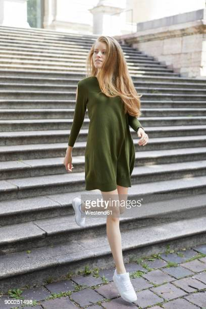 Portrait of young woman wearing green dress walking downstairs