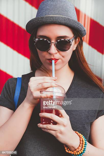 Portrait of young woman wearing hat and sunglasses drinking soft drink