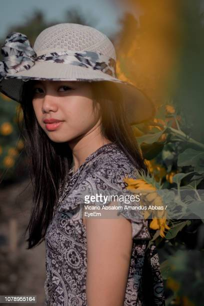 Portrait Of Young Woman Wearing Hat By Flowering Plants