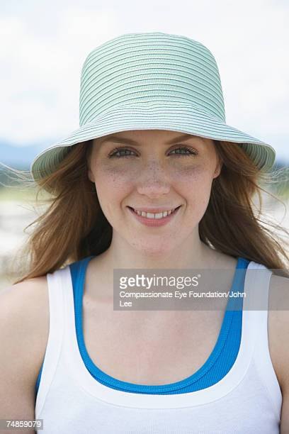 Portrait of young woman wearing hat on beach