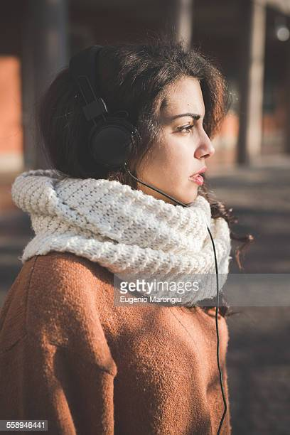 portrait of young woman wearing headphones in park - endast en ung kvinna bildbanksfoton och bilder