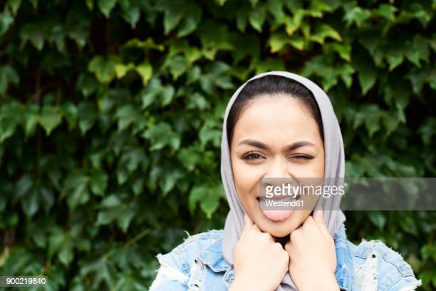 portrait of young woman wearing hijab stciking her tongue out - muslim rebel stock photos and pictures