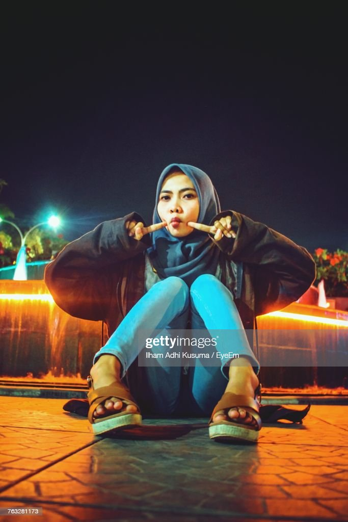Portrait Of Young Woman Wearing Hijab While Sitting On Footpath At Night : Stockfoto