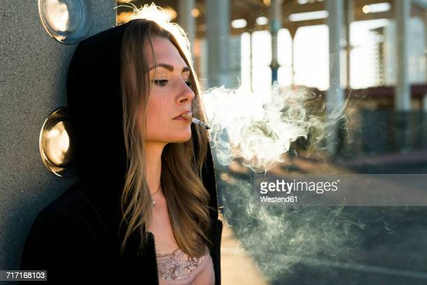 portrait of young woman wearing hooded jacket smoking cigarette at backlight - beautiful women smoking cigarettes stock photos and pictures