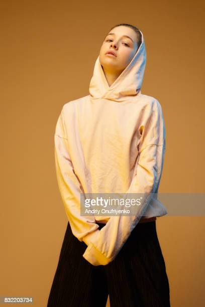 portrait of young woman wearing hoodie in studio - sweatshirt stock pictures, royalty-free photos & images