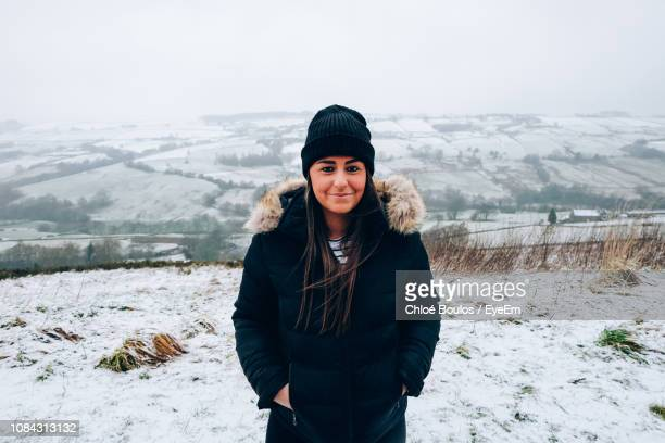 portrait of young woman wearing knit hat while standing on snow field against sky - winter coat stock pictures, royalty-free photos & images
