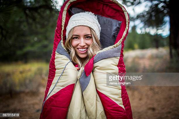 Portrait of young woman wearing knit hat wrapped in sleeping bag, Lake Tahoe, Nevada, USA