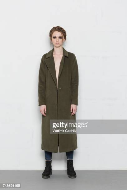 portrait of young woman wearing long coat standing against white background - coat ストックフォトと画像