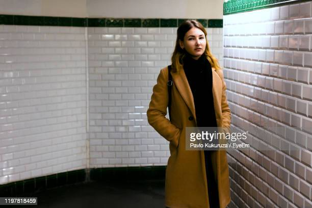 portrait of young woman wearing long coat standing by wall - long coat stock pictures, royalty-free photos & images