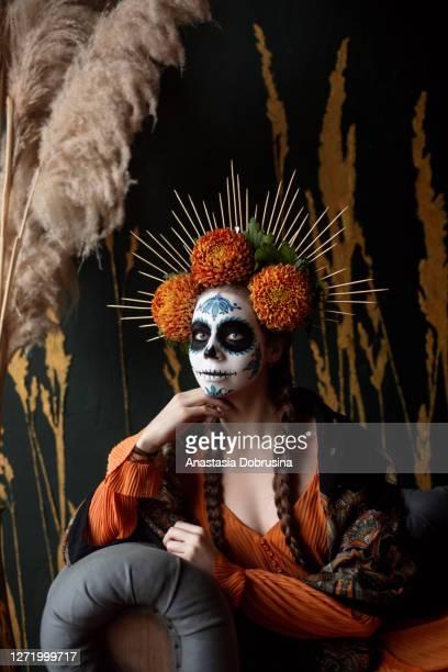 portret van jonge vrouw die make-up voor halloween draagt die door de mexicaanse viering wordt geïnspireerd. - struisvogelveer stockfoto's en -beelden