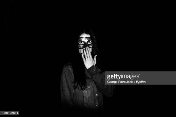 portrait of young woman wearing mask against black background - black mask disguise stock pictures, royalty-free photos & images
