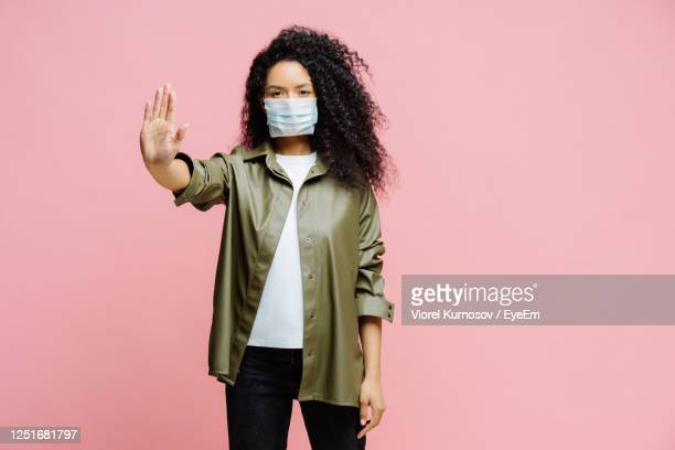 portrait of young woman wearing mask standing against pink background - gesturing stock pictures, royalty-free photos & images