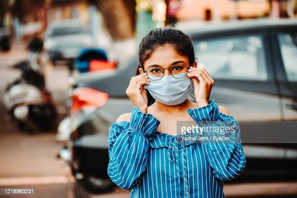 portrait of young woman wearing mask standing on street - india stock pictures, royalty-free photos & images
