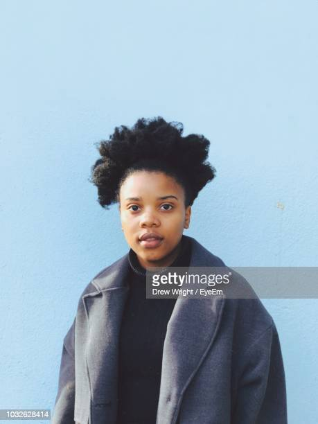 portrait of young woman wearing overcoat standing against wall - overcoat stock pictures, royalty-free photos & images