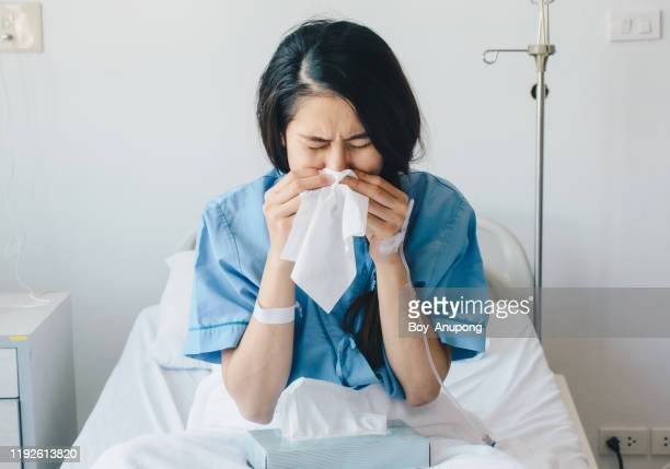 portrait of young woman wearing patient cloths sneezing in tissue at hospital. - iv drip womans hand stock pictures, royalty-free photos & images