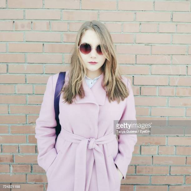 Portrait Of Young Woman Wearing Pink Overcoat By Brick Wall