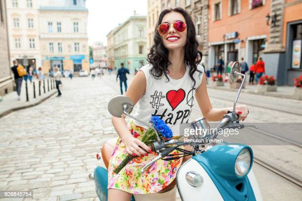 Portrait of young woman wearing pink sunglasses riding scooter on cobbled street, Odessa, Ukraine