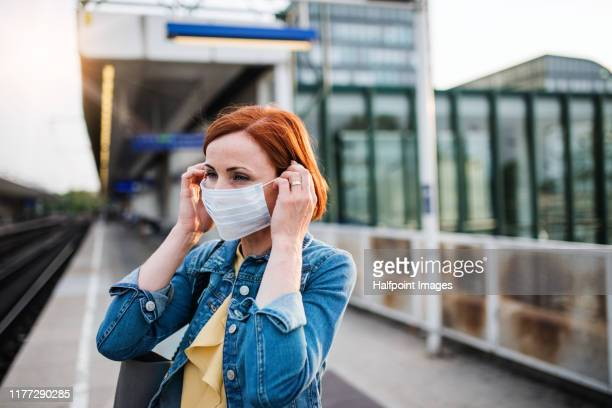 portrait of young woman wearing protective face mask outdoors in city. - cloth face mask stock pictures, royalty-free photos & images