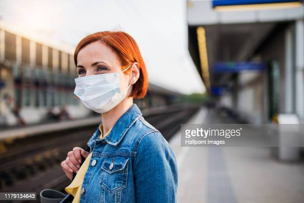 portrait of young woman wearing protective face mask outdoors in city, waiting for the train. - cubrebocas fotografías e imágenes de stock