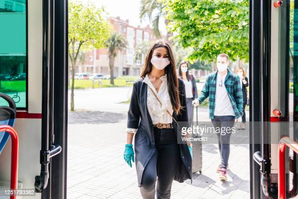 portrait of young woman wearing protective mask and gloves getting into bus, spain - eintreten stock-fotos und bilder