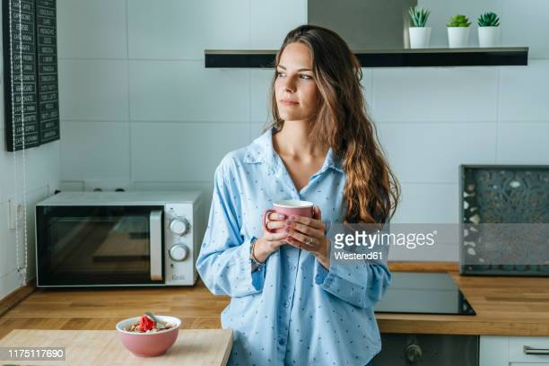 portrait of young woman wearing pyjama in kitchen at home holding cup of coffee - café bebida imagens e fotografias de stock