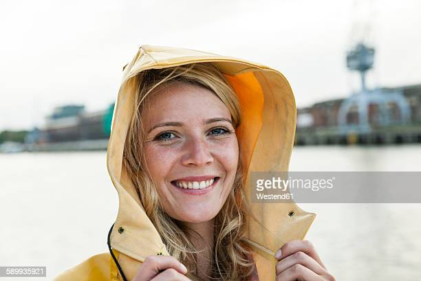 portrait of young woman wearing rain coat at the waterside - raincoat stock pictures, royalty-free photos & images
