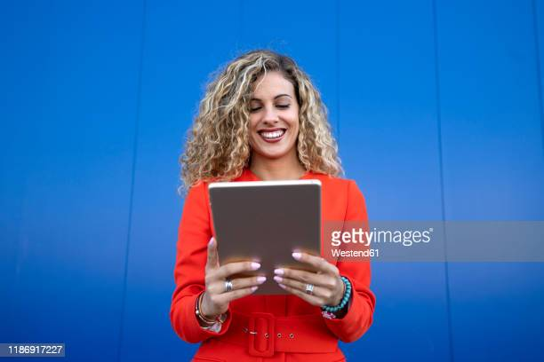 portrait of young woman wearing red dress in front of blue background using digital tablet - bright colour stock pictures, royalty-free photos & images