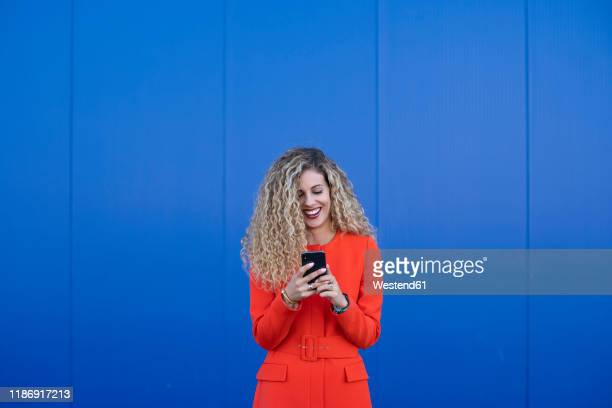 portrait of young woman wearing red dress using cell phone in front of blue background - portrait blue background stock pictures, royalty-free photos & images