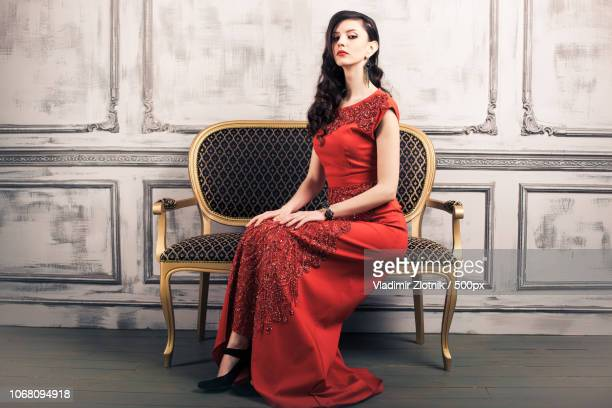 portrait of young woman wearing red evening gown - evening gown stock pictures, royalty-free photos & images