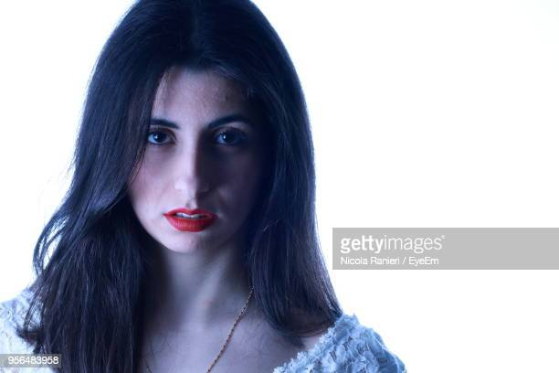 Portrait Of Young Woman Wearing Red Lipstick Against White Background