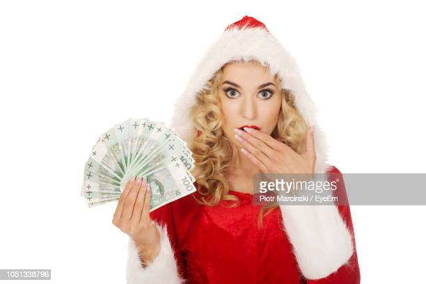 portrait of young woman wearing santa hat holding paper currencies against white background - christmas cash stock pictures, royalty-free photos & images