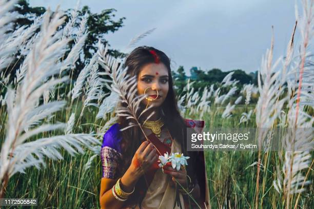 portrait of young woman wearing sari holding plant on land - sari stock pictures, royalty-free photos & images