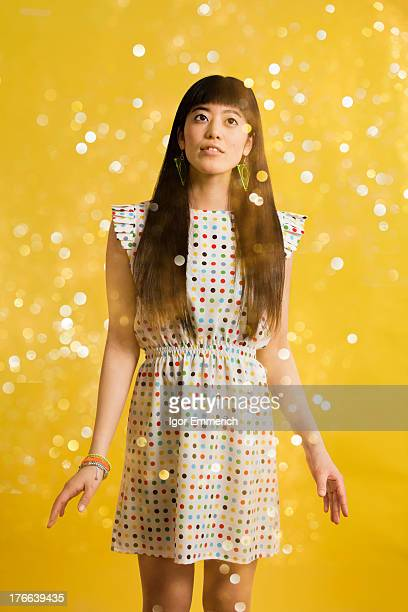 Portrait of young woman wearing spotted dress with glitter