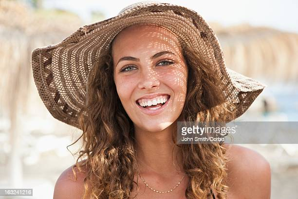 Portrait of young woman wearing straw hat on beach