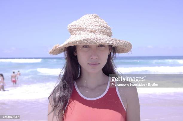 Portrait Of Young Woman Wearing Sun Hat Standing At Beach Against Clear Sky