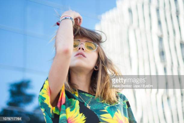 portrait of young woman wearing sunglasses against building - moda imagens e fotografias de stock