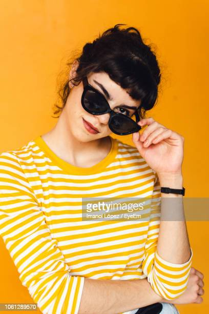 portrait of young woman wearing sunglasses against orange background - sunglasses stock pictures, royalty-free photos & images