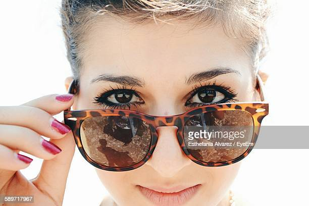 portrait of young woman wearing sunglasses against sky - サングラス ストックフォトと画像