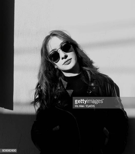 portrait of young woman wearing sunglasses and jacket against wall - aliai foto e immagini stock