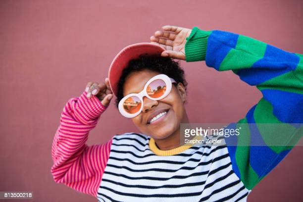 portrait of young woman wearing sunglasses - multi colored hat stock pictures, royalty-free photos & images