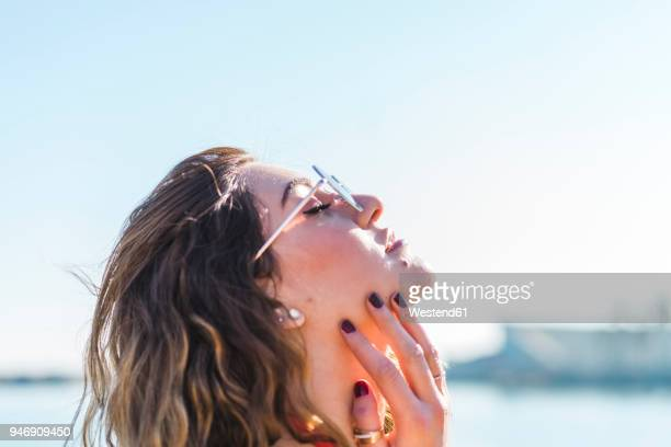 Portrait of young woman wearing sunglasses under blue sky