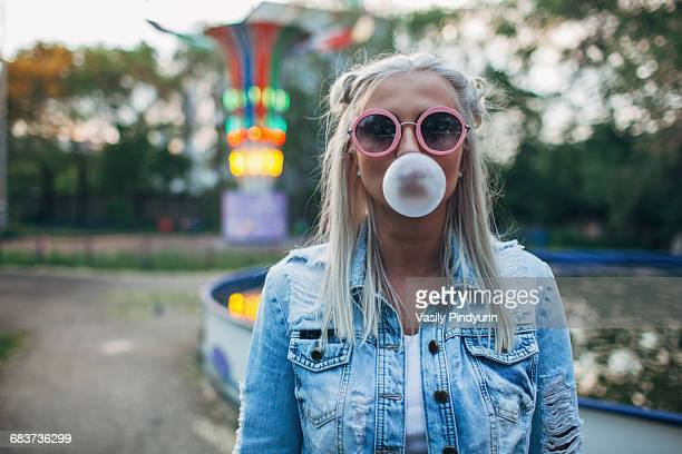 Portrait of young woman wearing sunglasses while blowing bubble gum at amusement park