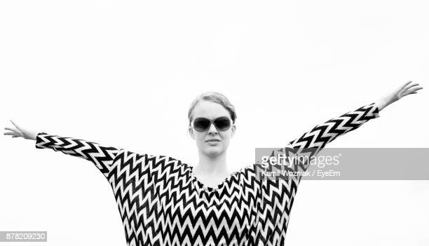 Portrait Of Young Woman Wearing Sunglasses With Arms Outstretched Standing Against White Background