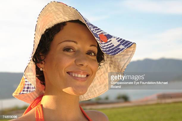 Portrait of young woman wearing sunhat, smiling