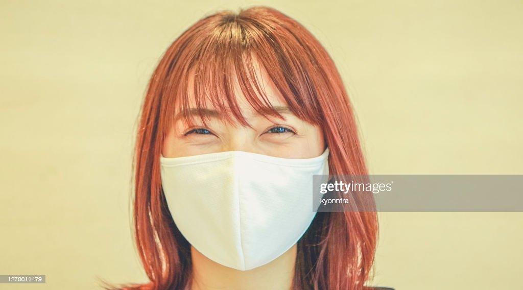 笑顔の外科マスクを身に着けている若い女性の肖像画 : ストックフォト